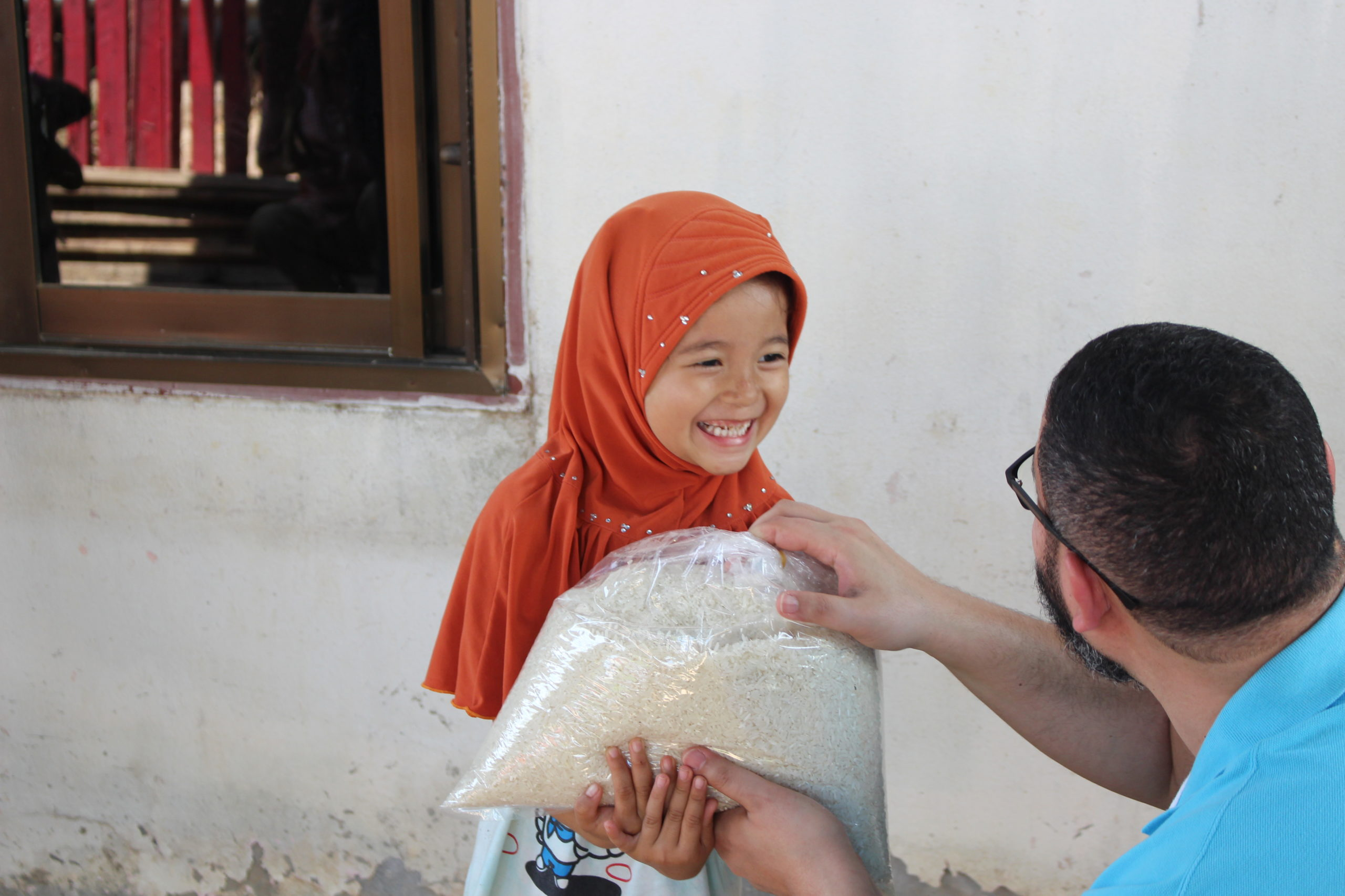 La petite fille ne peut cacher son sourire en recevant le riz.