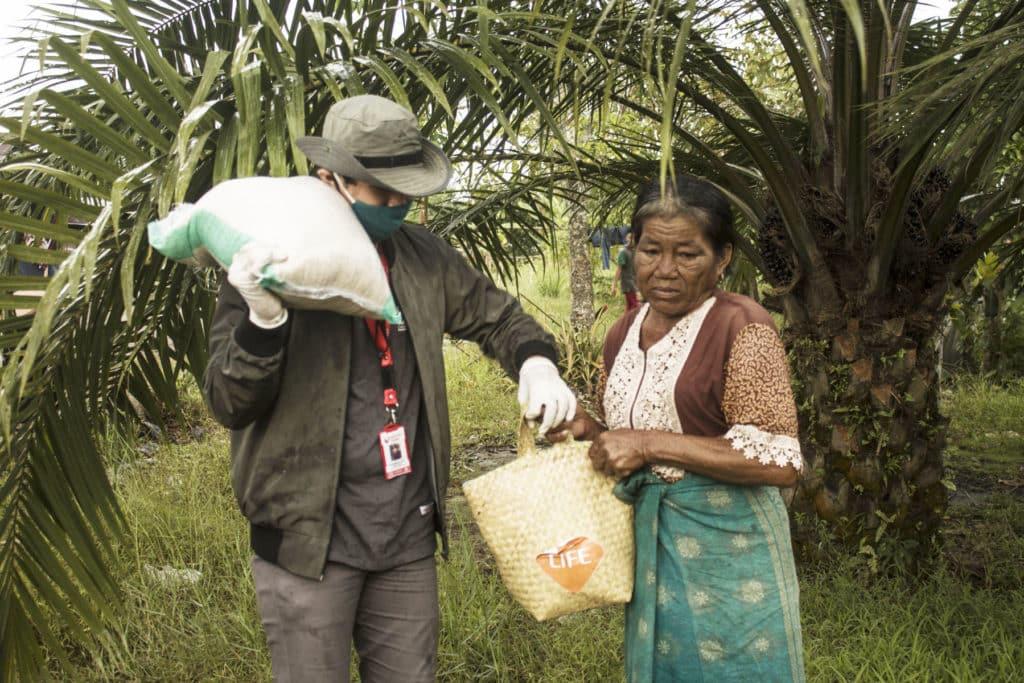 Une femme âgée bénéficie d'un colis de nourriture - association life ong